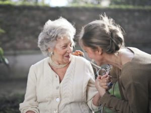 An aging parent wearing white is smiling at a woman in brown who is leaning