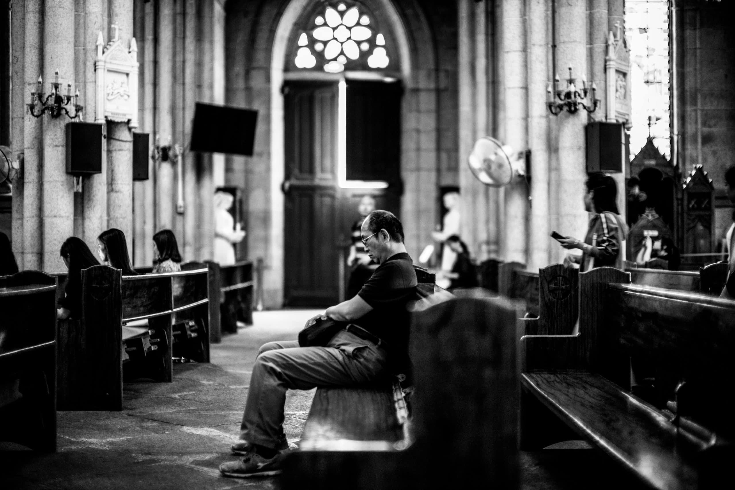 Socially distanced church attendees sit quietly